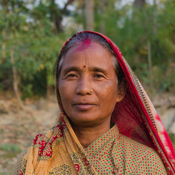 Portrait in forest of Chairwoman in Nepal looking at camera