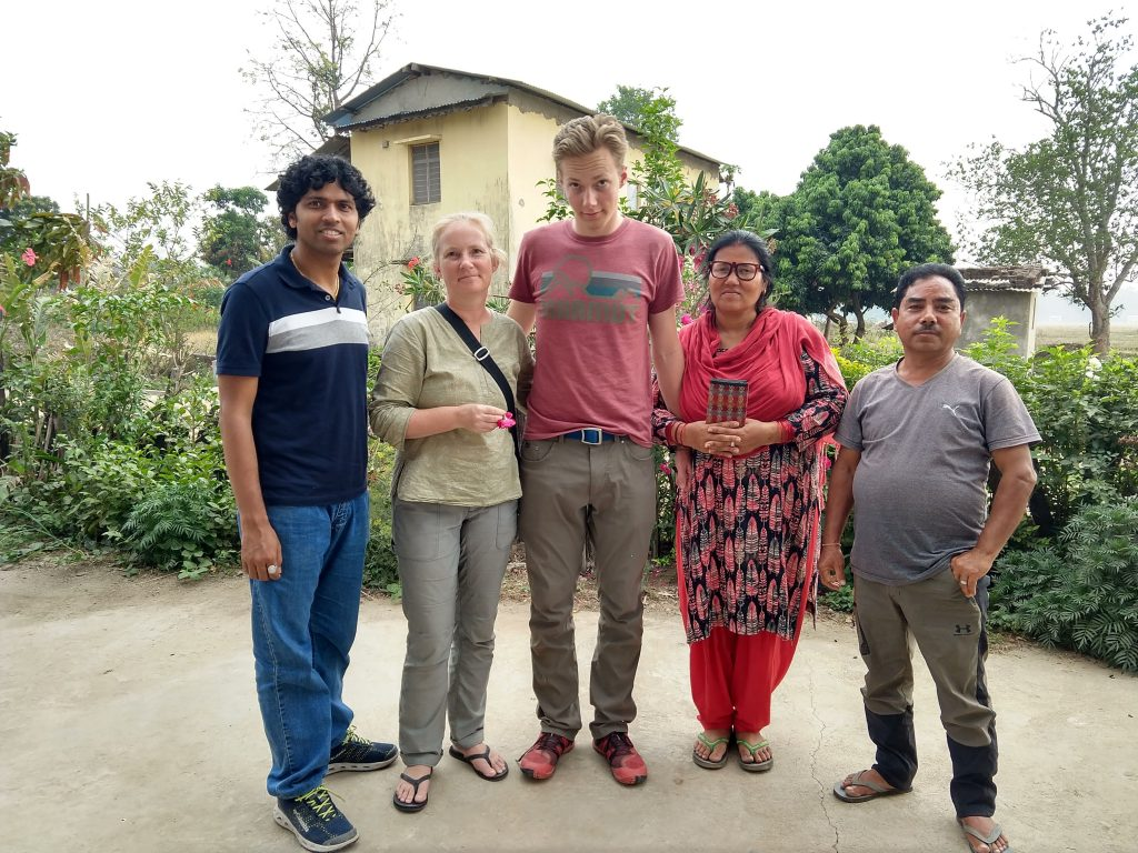 Conservation workers standing together and smiling in front of a garden and house