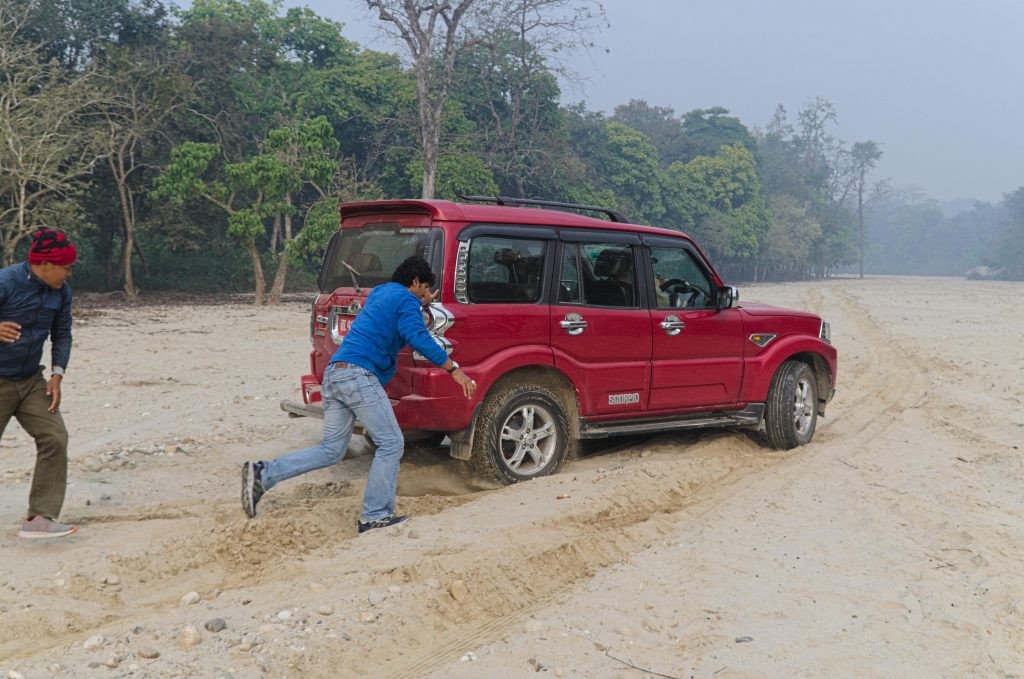 Two men running while pushing a red truck through sand with deep tire grooves