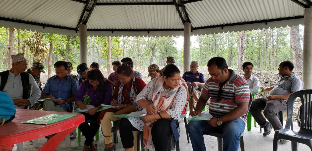 Group of trainees in Nepal at wildlife training session sit in open-air training pavilion and listen to speaker while taking notes
