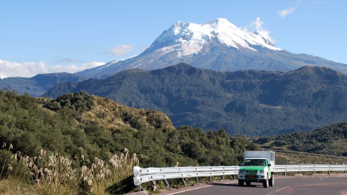 Large snow-capped volcano in Ecuador with truck driving in foreground - Volcan Antisana