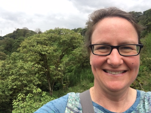 Selfie of Conservationist Dr. April Sansom in front of a forest vista in Ecuador 2019