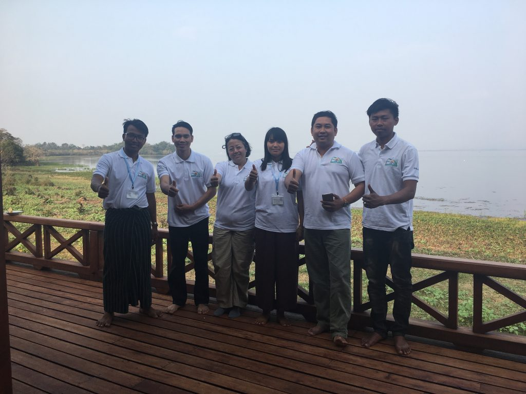 Group of young people stand together on deck overlooking water with matching polo shirts giving a thumbs up
